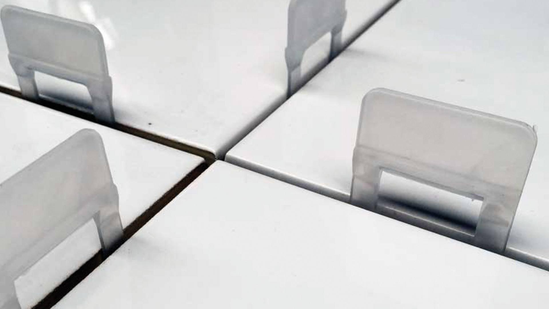 Erste Fliese wie gewohnt verlegen, Laschen unter Fliese stecken und benachbarte Fliese anlegen.