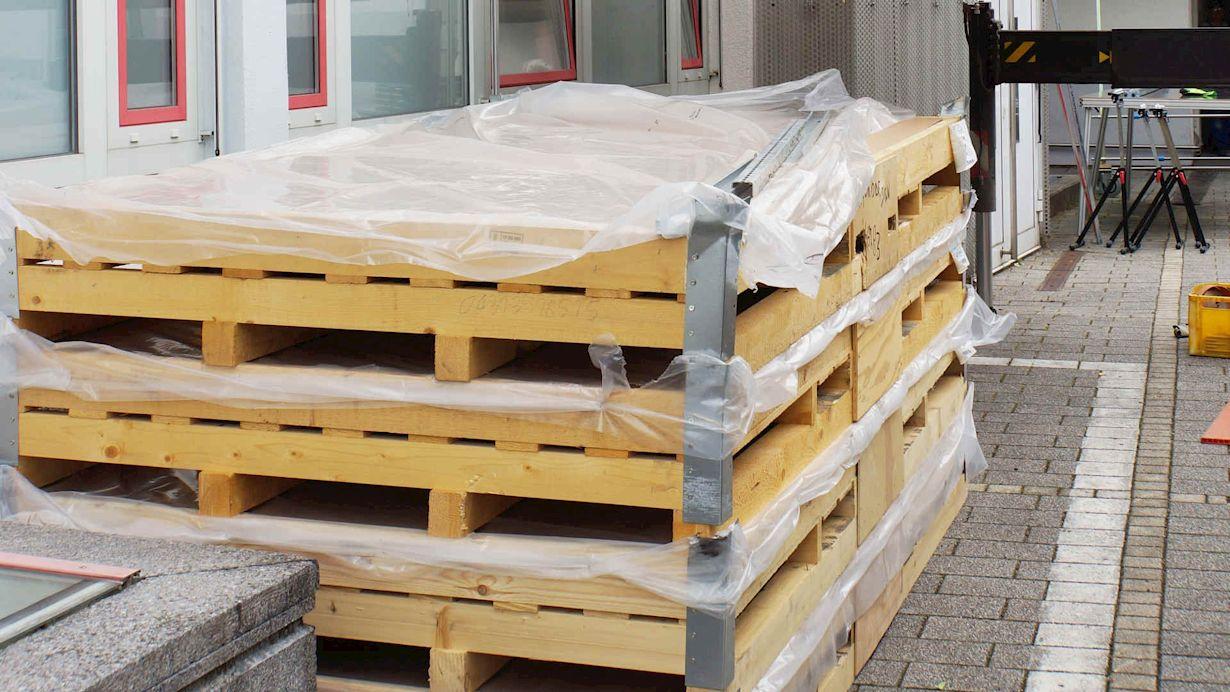 Die großen Fliesen werden liegend in Kisten zur Baustelle geliefert.